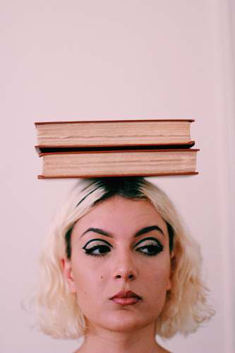 person two books on top of woman's head human