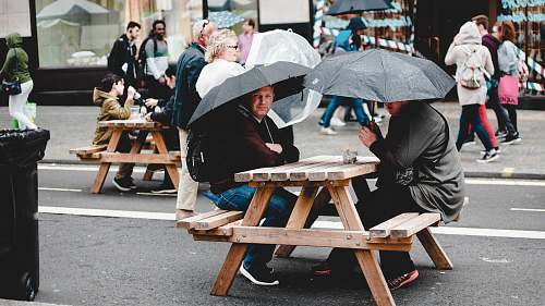 human two man seating on brown picnic table under black umbrella person