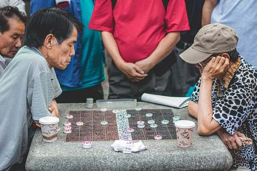 cup two men sitting beside table playing game game