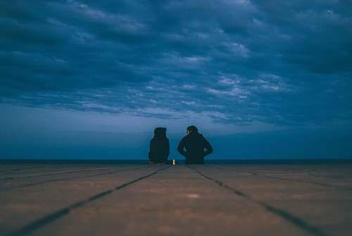 blue two people wearing black jackets sitting on floor water