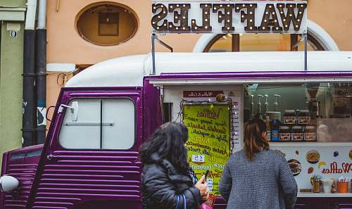 human two women near purple and white waffle van with store at daytime person