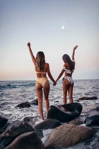 human two women standing on rock while raising their hands near sea during daytime person