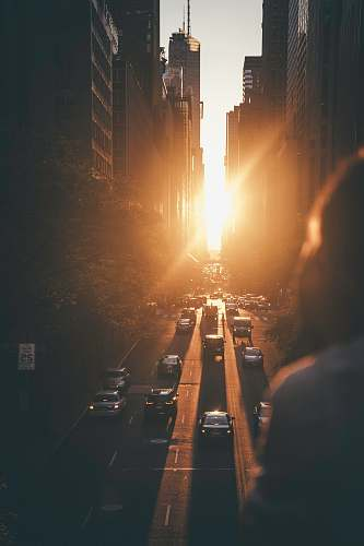 human vehicles passing between buildings during sunset person