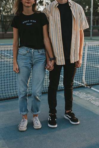 human woman and man standing side by side while holding hands in tennis court person