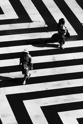 black-and-white woman and man waling on white and black striped road road