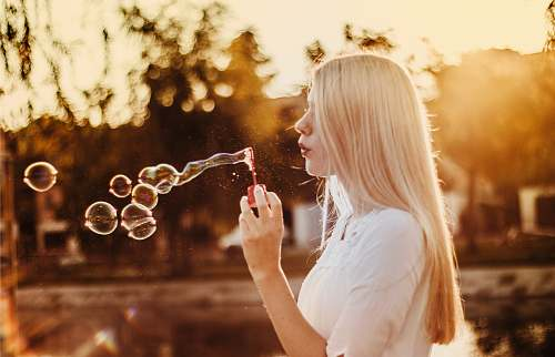 human woman blowing bubbles during sunset bubble
