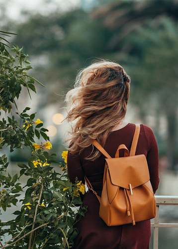 human woman carrying brown leather backpack person