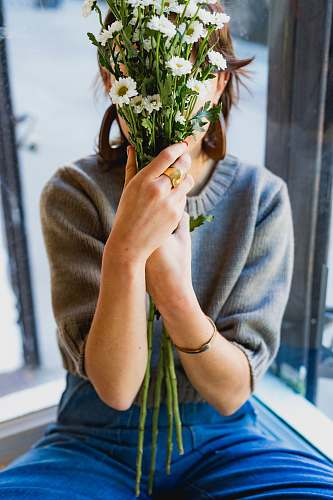 person woman covering her face with white flowers human
