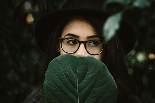 human woman covering her mouth with green leaf glasses