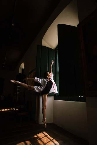 person woman doing ballet pose in front of window during daytime dance
