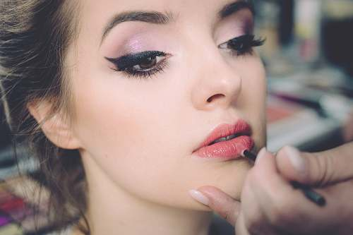 beauty woman getting lips applied with lipstick makeup
