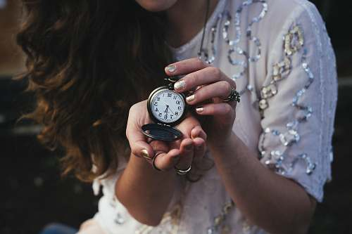 human woman holding black pocket watch at 5:30 time