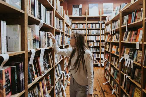 person woman holding book on bookshelves book