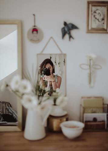 human woman holding DSLR camera taking photo in front mirror inside room person
