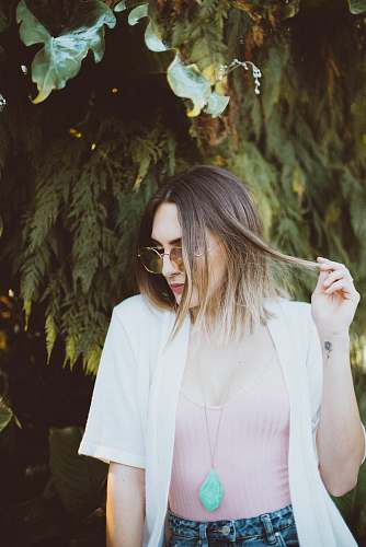 human woman holding her hair while looking sideways person