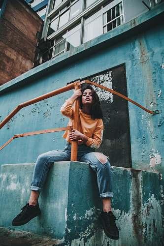 human woman hugging post of orange metal railings during day person