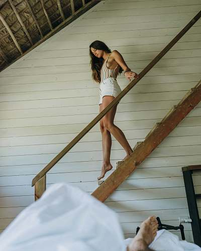 human woman in beige spaghetti strap camisole and white short shorts walking down on stair person