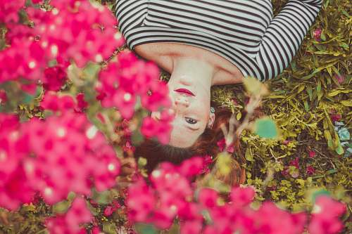 person woman in black and white striped top lying on grass face