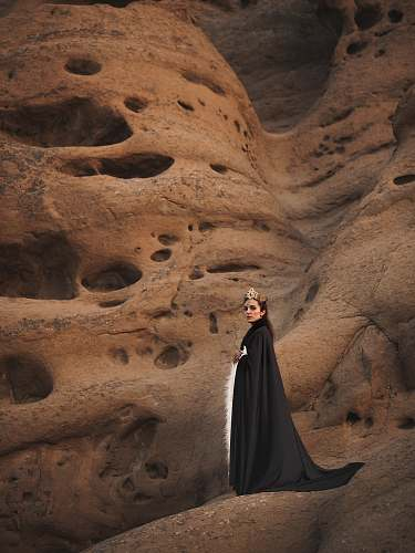 human woman in black cape standing on brown mountain person
