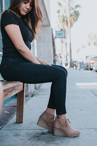 person woman in black t-shirt and black pants sitting on brown wooden bench during daytime human