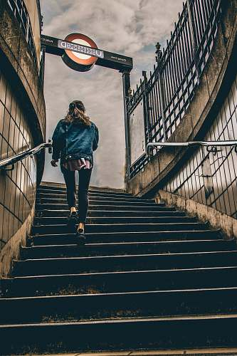 person woman in blue denim button-up jacket walking on concrete stairs during daytime london