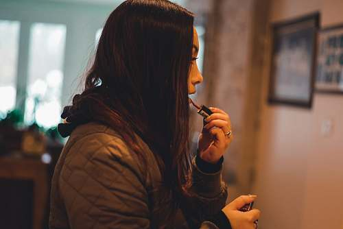 human woman in brown quilted hoodie holding lipstick shallow focus photography person