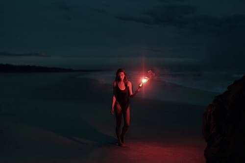 human woman in one-piece swimsuit holding torch person