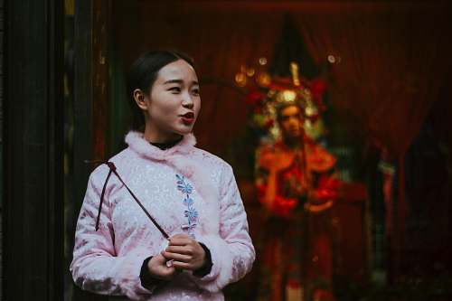 human woman in pink sweatshirt holding stick shallow focus photography temple