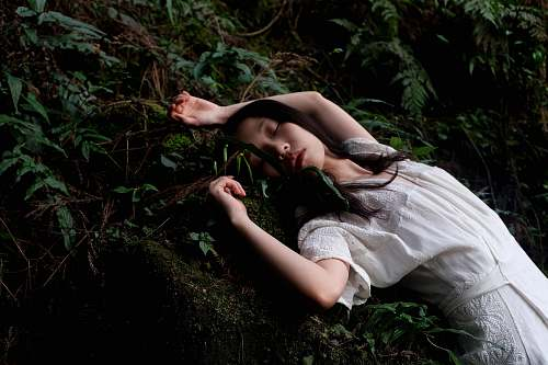 woman woman in white dress lying in white dress forest