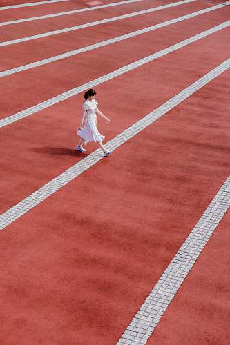 human woman in white dress walking on track and field person
