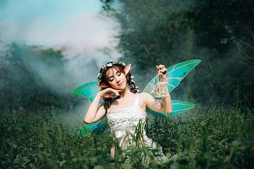 human woman in white dress wearing green fairy wings person