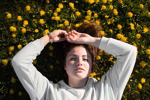 person woman in white top laying on flowers caucasian