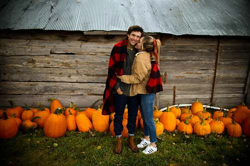 human woman kissing man near pumpkins person