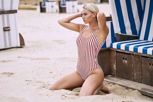 woman woman kneeling down on sand swimwear