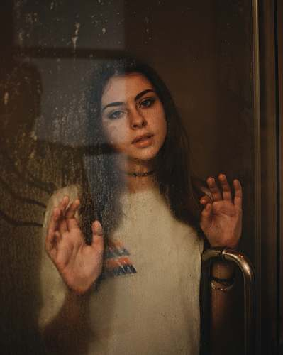 person woman leaning on glass door human