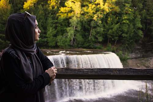 person woman leaning on railings near waterfalls human
