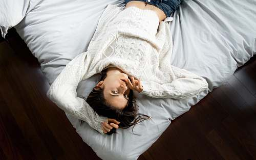 person woman lying on bed with white bedspread human