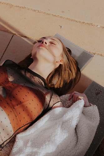human woman lying on brown concrete pavement person