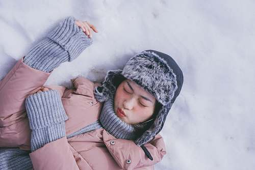 human woman lying on white snow during daytime person