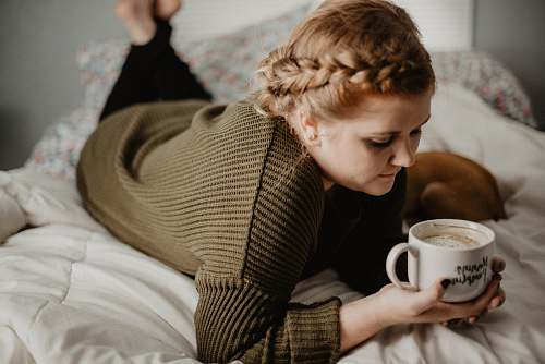 human woman on bed holding white mug person