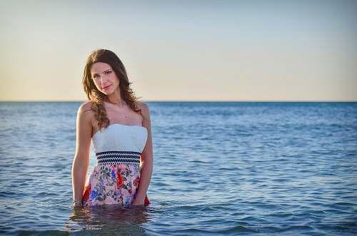 person woman on ocean wearing dress talking photo during sunset human