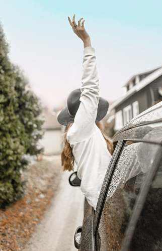 human woman rising left hand on vehicle window during daytime person