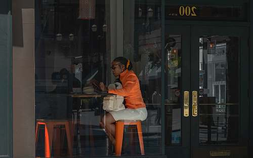 person woman sitting in front of brown table door