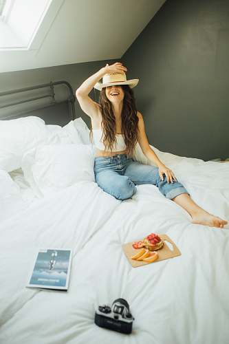 human woman sitting on bed holding her hat person