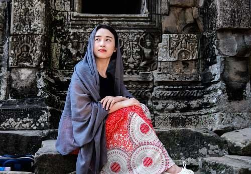 human woman sitting on concrete stone person