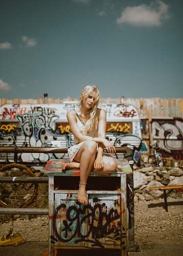 graffiti woman sitting on multicolored end table outdoor girl