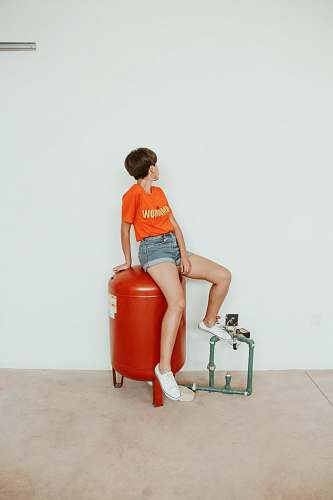 human woman sitting on red metal tank person