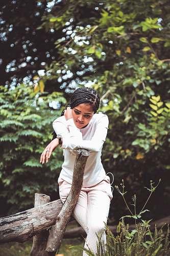 human woman sitting on tree log during daytime person