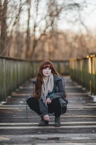 person woman sitting on wooden bridge human