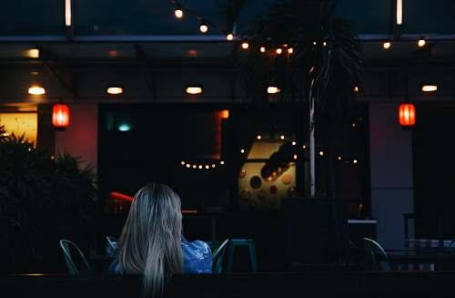 person woman sitting while facing towards bar singapore